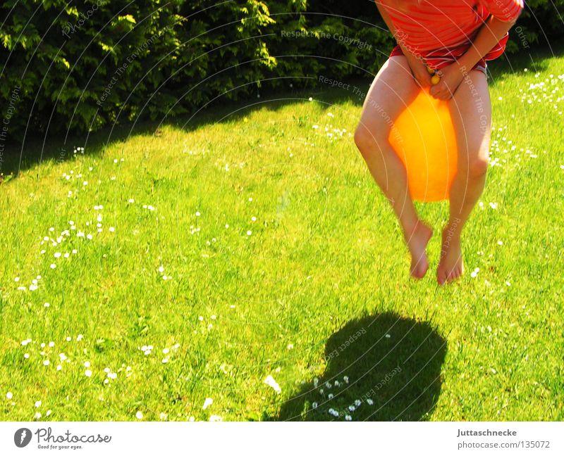 Känguruh Kind Junge Spielen Spielzeug hüpfen springen gelb grün Wiese Gras Sport Freude Hüpfball Känguruhball Garten Rasen lustig Schatten hoch Lausejunge