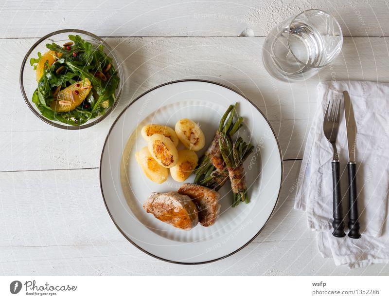 Schweinemedaillons mit Kartoffeln und Bohnen Küche Gemüse heiß Teller Fleisch Holztisch Besteck Gabel Saucen Feinschmecker Wasserglas knusprig gebraten