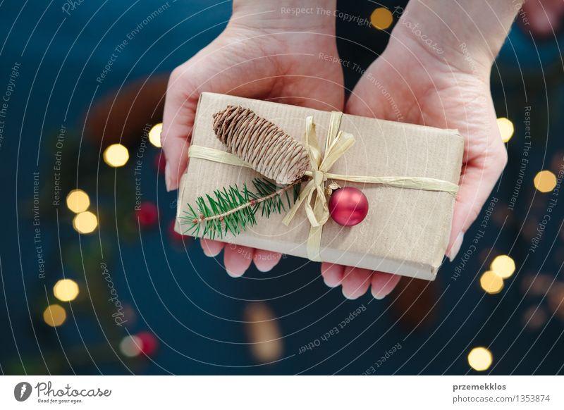 Frau hält Weihnachtsgeschenk Erwachsene Hand Papier Verpackung Kasten Schnur Kultur Tradition Gast Dezember Geschenk heimwärts horizontal Kiefer umhüllen