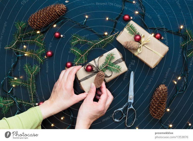 Frau, die Weihnachtsgeschenke einwickelt Schere Erwachsene Hand Papier Kasten Schnur Kultur Tradition Gast Dezember Geschenk heimwärts horizontal Kiefer