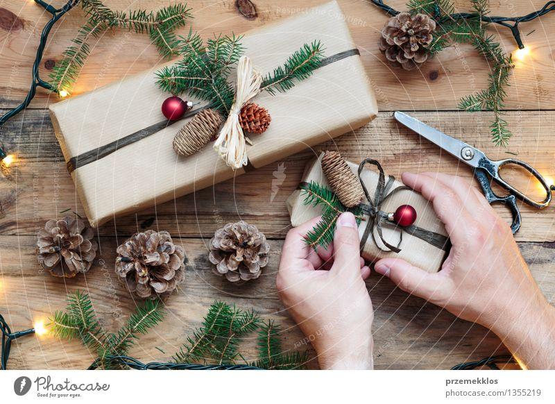 Dekorieren von verpackten Weihnachtsgeschenken Schere Hand Papier Paket Kasten Schnur Tradition Dezember Geschenk heimwärts horizontal Kiefer umhüllen Farbfoto