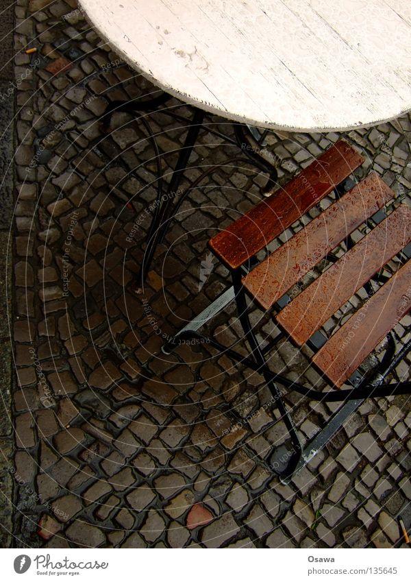 Schwarzes Cafe Café Straßencafé Tisch Möbel Regen nass Regenwasser Bürgersteig Kopfsteinpflaster ungemütlich Stuhl Sitzgruppe Wasser ins Wasser gefallen