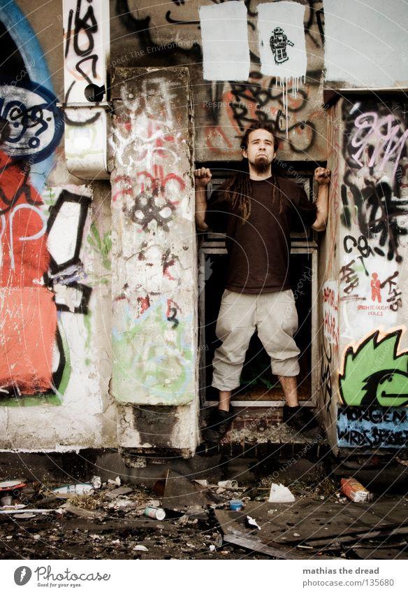 SCHAUFENSTER dreckig mehrfarbig durcheinander Scherbe kaputt Fenster stehen Suche Ferne Mann kurz Hose braun Rastalocken Schuhe parallel rot grün schwarz weiß