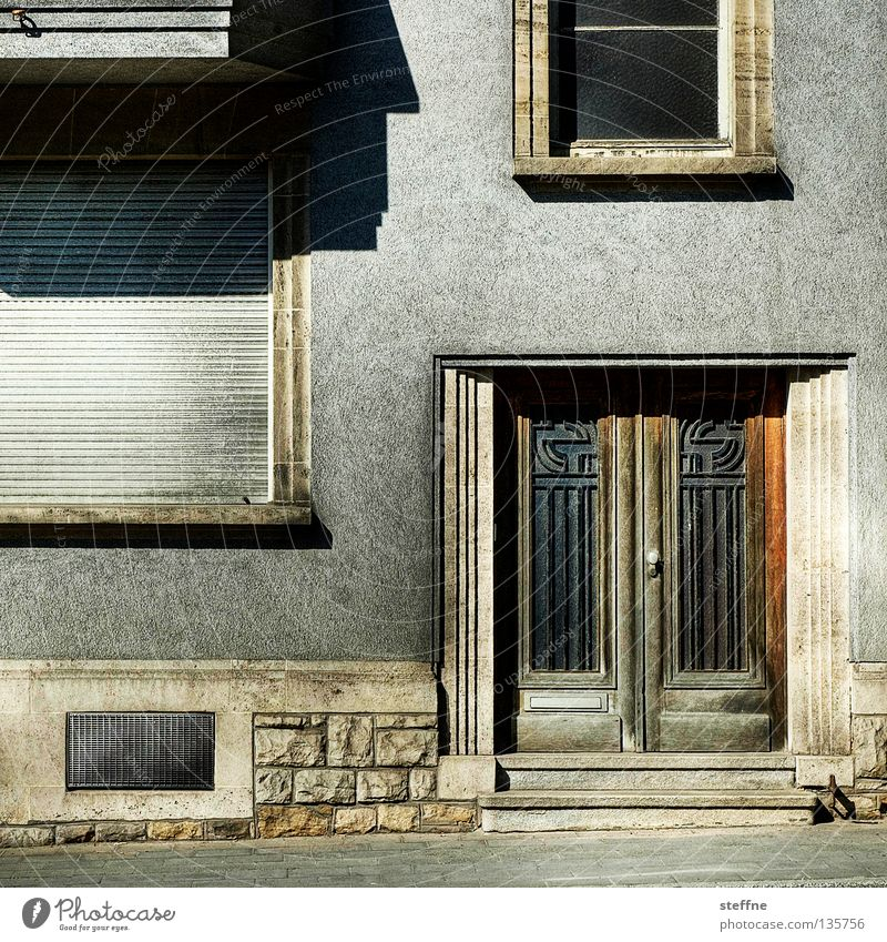 Wohnform Fassade Haus Wohnung Einfamilienhaus Wand Mauer Putz Eingangstür Rollladen Kellerfenster Fenster Treppenhaus trist altmodisch Wohnsiedlung Stadt