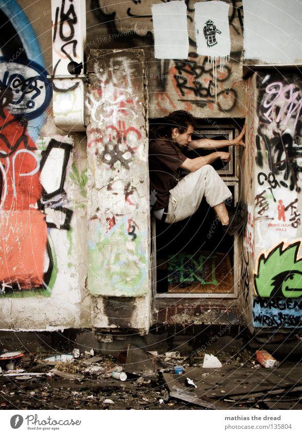 NEXT ONE dreckig mehrfarbig durcheinander Scherbe kaputt Fenster stehen Suche Ferne Mann kurz Hose braun Rastalocken Schuhe parallel rot grün schwarz weiß