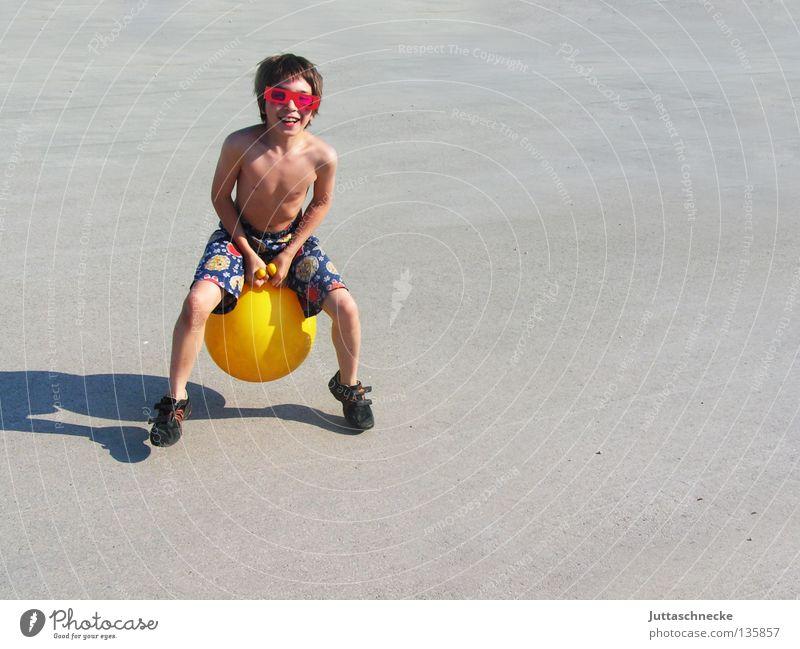 Häschen hüpf Kind Junge Spielen Spielzeug hüpfen springen Känguruh gelb Brille Sonnenbrille retro Sommer Freude Hüpfball Känguruhball lustig Schatten hoch