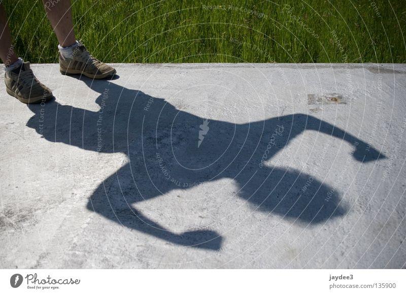 Superschatten Sonne Sommer Gras grau Schuhe Beine Kraft stark Held Muskulatur Superman Schattenspiel