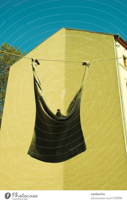 Einsames Hemmed Hemd Einsamkeit Wäsche Wäscheleine Wäschetrockner trocken Venus Haus Fassade Wand seltsam Detailaufnahme obskur Sommer Seil wäsche aufhängen