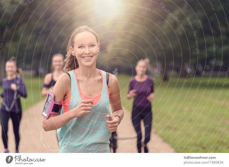 Athletische hübsche junge Frau, die mit Freunden trainiert Hund Sommer Erholung Erwachsene Sport Glück Lifestyle Menschengruppe Zusammensein Freundschaft Park