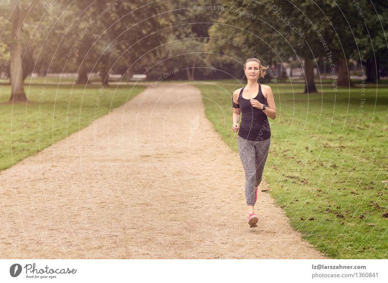Athletische Frau, die in einem Park trainiert Sommer Sport Joggen Erwachsene Natur Tatkraft Aktion sportlich Herz Textfreiraum üben Gesundheit Jogger Läufer