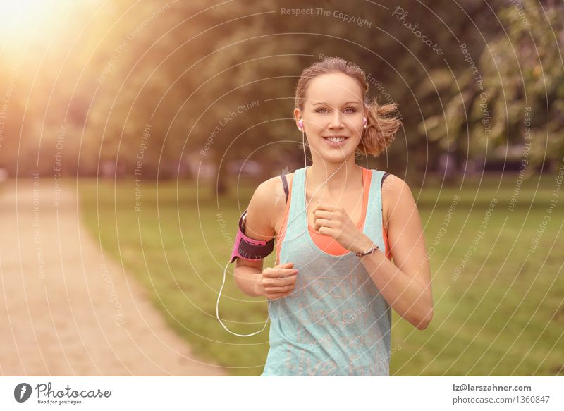 Recht athletische Frau, die in einen Park läuft Lifestyle Glück Sommer Musik Sport Joggen Erwachsene Landschaft Herbst Blatt Straße Bewegung Fitness hören