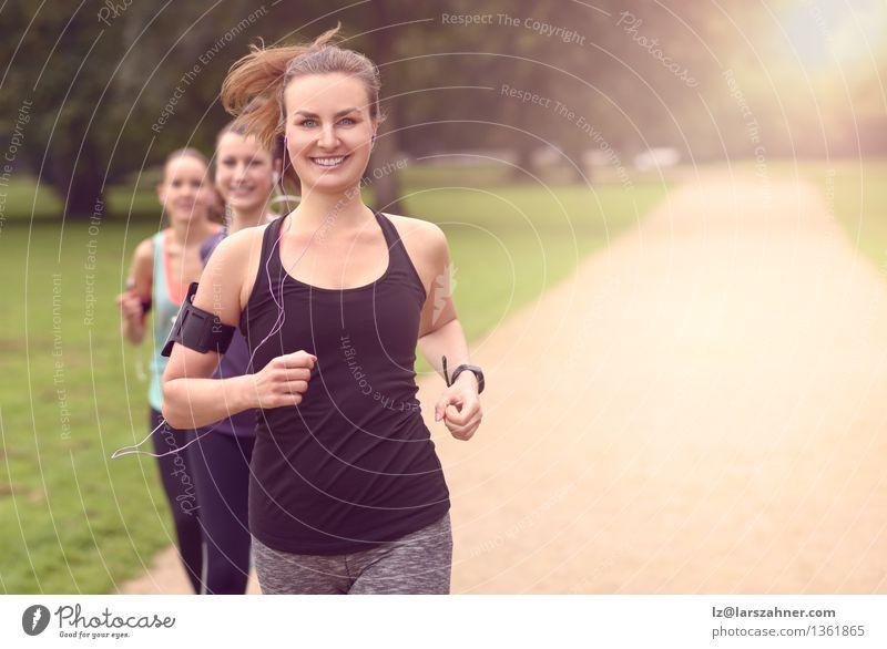 Athletische hübsche junge rüttelnde Frauen Lifestyle Erholung Sommer Musik Sport Joggen Telefon PDA Erwachsene Freundschaft Arme Menschengruppe Band Park
