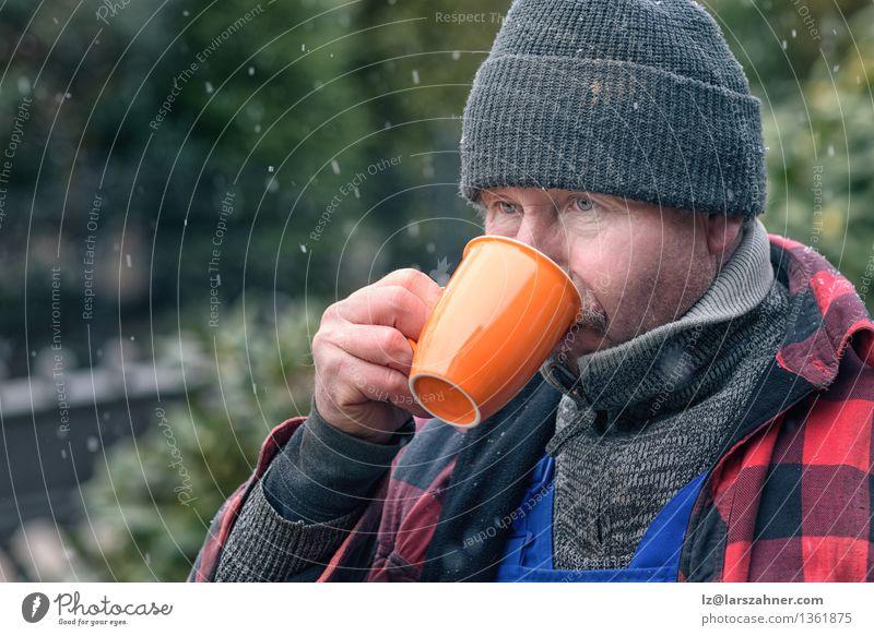 Mann in trinkendem Kaffee der gestrickten Wollmütze Getränk Gesicht Winter Schnee Handwerker Erwachsene Wetter Wärme Jacke Schal Hut heiß Konzentration Beanie