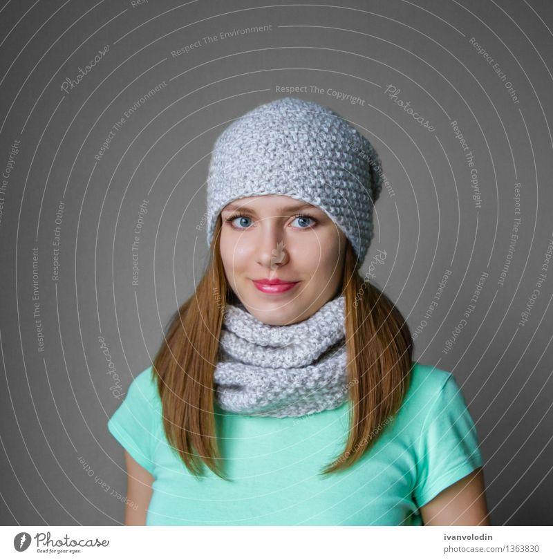 Lächelndes junges Mädchen in der Winterkappe und -schal Freude Glück schön Haut Gesicht Kosmetik Mensch Frau Erwachsene Wärme Mode Bekleidung Pullover Schal