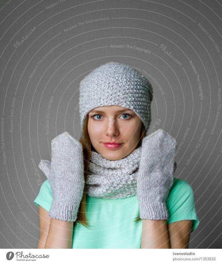 Lächelndes junges Mädchen in der Winterkappe, -schal und -handschuhen Mensch Frau Jugendliche grün schön Junge Frau weiß Hand Freude 18-30 Jahre Gesicht