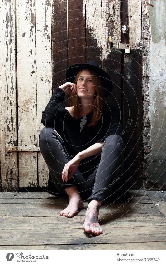 lässig Lifestyle Stil schön Junge Frau Jugendliche Körper Fuß Barfuß Model Dachboden Holztür Holzwand Jeanshose Hut rothaarig langhaarig Lächeln lachen sitzen