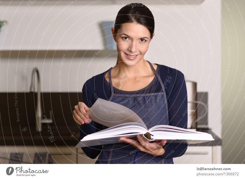 Junge Frau in einem Schutzblech, das oben ein Rezept schaut Mensch Gesicht Erwachsene natürlich Glück Lifestyle Zufriedenheit modern Kreativität Lächeln Buch