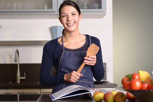 Frau, die Schöpflöffel beim Ablesen eines Kochbuchs hält Mensch Gesicht Erwachsene natürlich lachen Glück Denken Frucht modern Ernährung Lächeln Buch