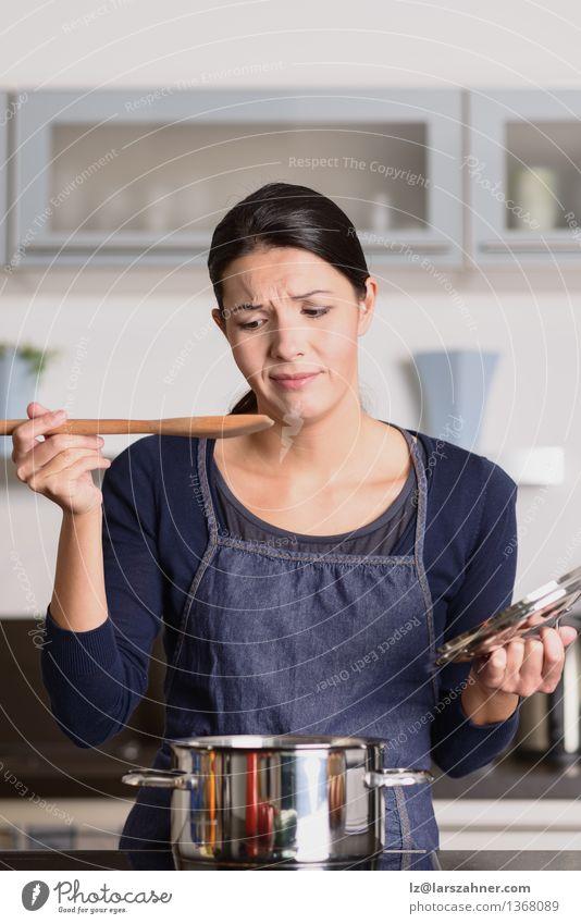 Junger Koch, der ihr Lebensmittel mit einer Grimasse schmeckt Abendessen Topf Löffel Gesicht Küche Frau Erwachsene 1 Mensch 30-45 Jahre heiß Wut attraktiv