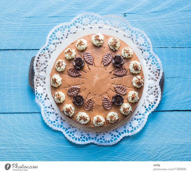 Schokosahnetorte auf blauem Holz mit Tortenspitze Kuchen Dessert Schokolade Schokoladen-Sahne-Torte Schaumgebäck Backwaren Biskuit Holztisch rustikal