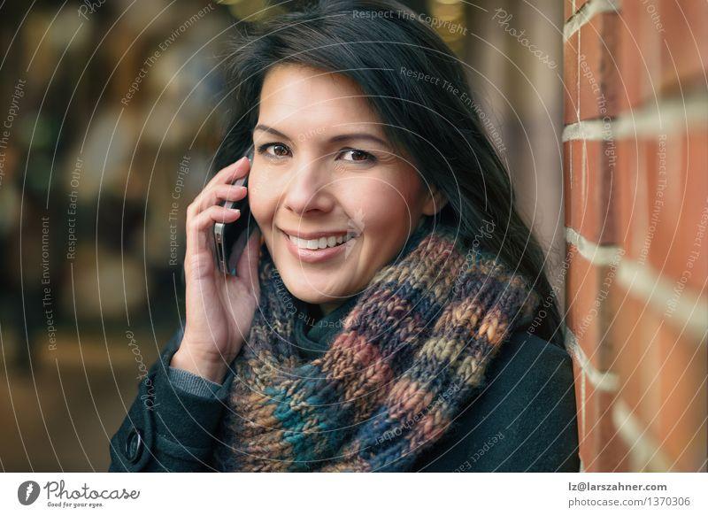 Lächelnde Frau in Autumn Fashion Talking am Telefon Lifestyle Glück schön Gesicht Winter sprechen PDA Erwachsene Herbst Stadt Straße Mantel Schal brünett