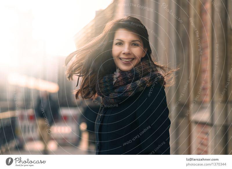 Glückliche Frau mit einem reizenden Lächeln auf einer Winterstraße Mensch Natur Stadt Sonne Freude Gesicht Erwachsene Straße Herbst Bewegung Lifestyle Freiheit