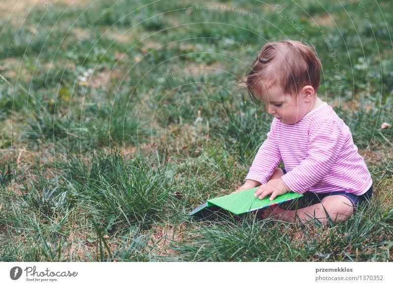 Kleines Baby, das ein Buch mit Bildern überwacht Lifestyle Freude Glück schön Leben Spielen Kind Mensch Kleinkind Mädchen Kindheit 1 0-12 Monate Gras Garten