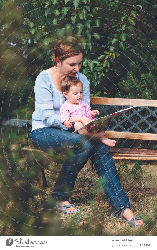 Mutter, die ein Buch ihre kleine Tochter liest Lifestyle Freude Glück schön Leben Spielen lesen Garten Kind Baby Kleinkind Mädchen Frau Erwachsene Eltern