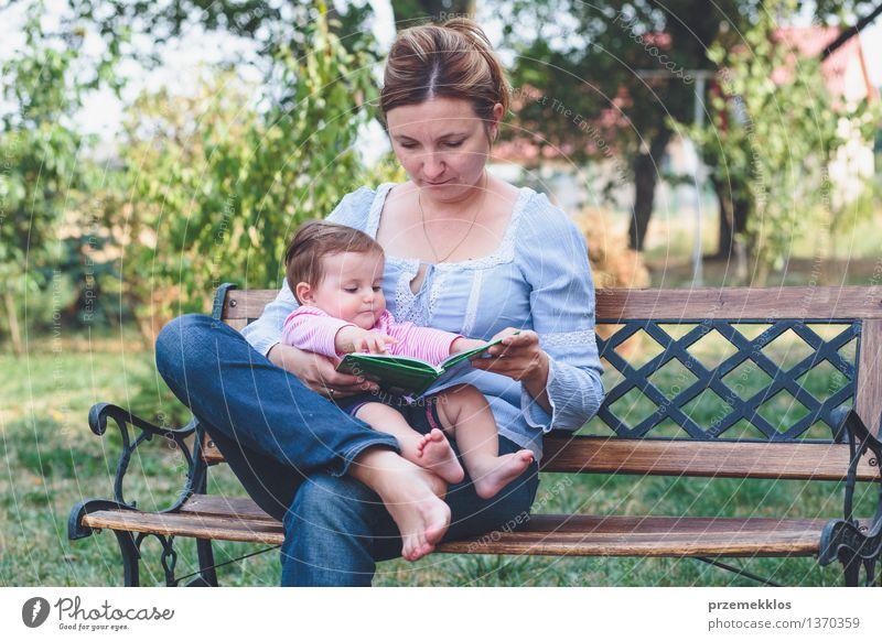 Mutter, die ein Buch ihre kleine Tochter liest Lifestyle Freude Glück schön Leben lesen Garten Kind Baby Kleinkind Mädchen Frau Erwachsene Eltern