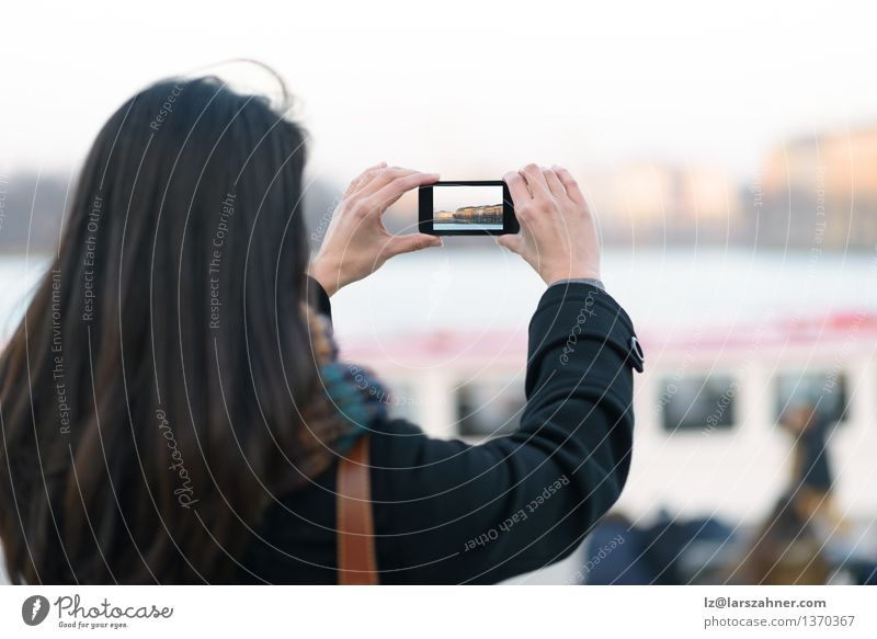 Frau, die Ansicht im Freien unter Verwendung des Handys nimmt Ferien & Urlaub & Reisen Winter Erwachsene Deutschland Tourismus Behaarung modern Aussicht