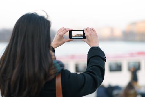 Frau, die Ansicht im Freien unter Verwendung des Handys nimmt Ferien & Urlaub & Reisen Tourismus Ausflug Winter Telefon PDA Bildschirm Fotokamera