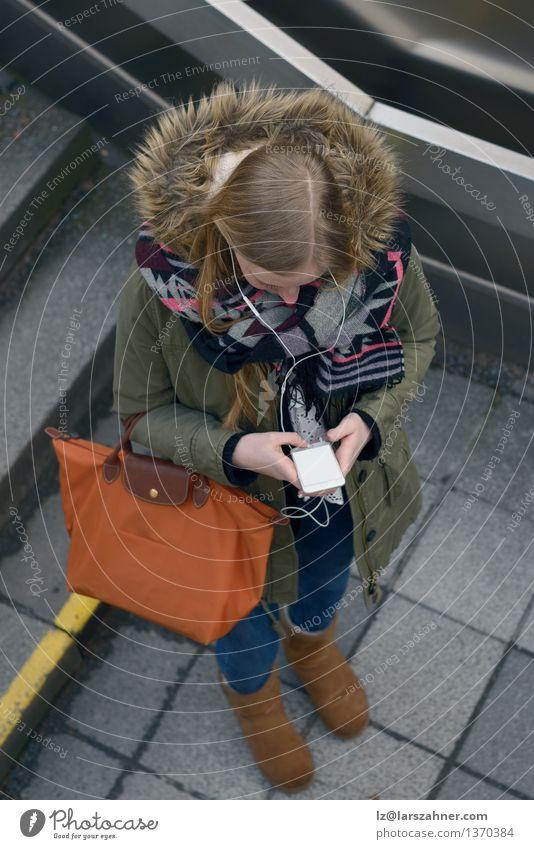 Junge Frau, die sms auf ihrem Mobile überprüft Mensch Jugendliche Winter Erwachsene Herbst oben 13-18 Jahre blond stehen Technik & Technologie lesen Telefon