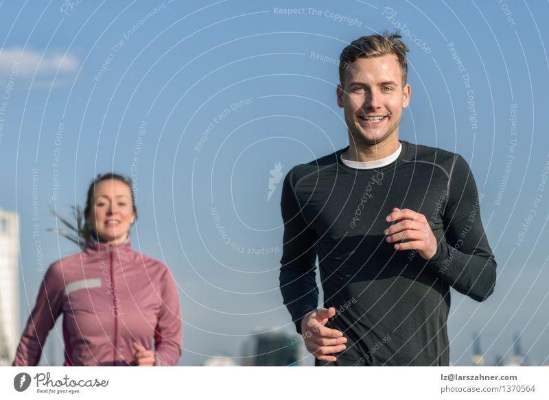 Lächelnder gutaussehender Mann, der mit seiner Frau rüttelt Mensch Himmel Jugendliche blau Erholung 18-30 Jahre Gesicht Erwachsene Bewegung Sport Glück