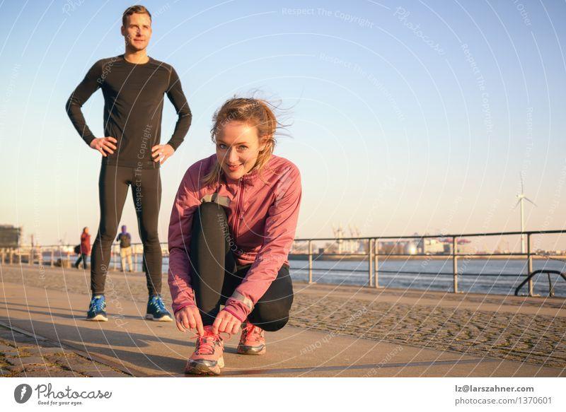 Sportliches aktives Paar auf einer Strandpromenade Lifestyle Joggen Arbeit & Erwerbstätigkeit maskulin feminin Frau Erwachsene Mann 2 Mensch 18-30 Jahre