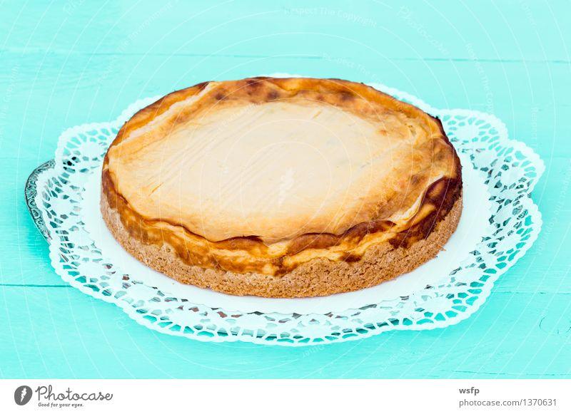Käsekuchen auf türkisem Holz mit Tortenspitze Kuchen Dessert Quarkkuchen Quarktorte Backwaren Biskuit Holztisch Landhaus rustikal Hintergrund neutral 1 lecker