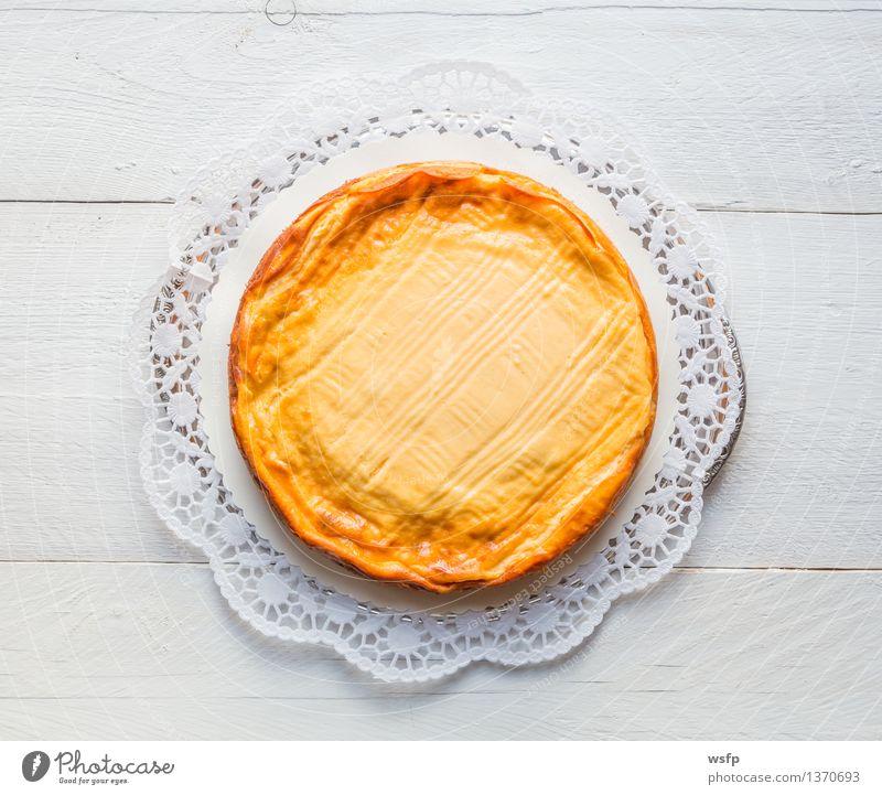 Käsekuchen auf weißem Holz mit Tortenspitze Kuchen Dessert Quarkkuchen Quarktorte Backwaren Biskuit Holztisch rustikal Vogelperspektive Süßwaren rund lecker