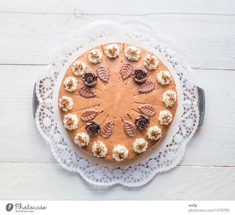 Schokosahnetorte auf weißem Holz mit Tortenspitze Kuchen Dessert Schokolade Schokoladen-Sahne-Torte Schaumgebäck Backwaren Biskuit Holztisch rustikal