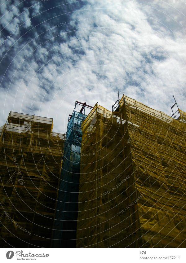 DISGUISE blau Stadt gelb Fassade Baustelle Schutz Vergänglichkeit Handwerk verstecken bauen Renovieren Baugerüst bedecken Sanieren Abdeckung zudecken