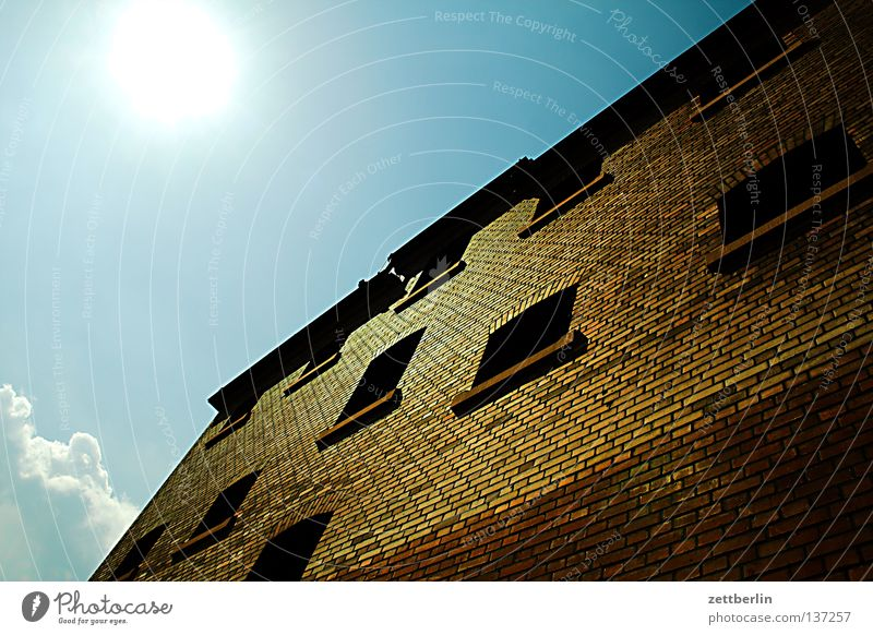 Gehe ins Gefängnis! Haus Wand Fassade steil eng Platzangst Fenster Gitter Justizvollzugsanstalt Haftstrafe Backstein himmelblau Gegenlicht blenden grell Wolken