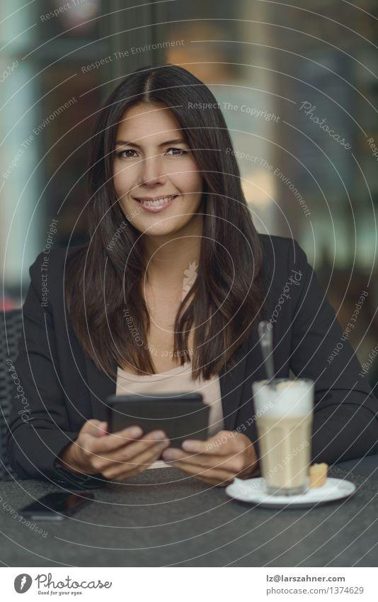 Lächelnde Frau in der Kaffeestube Erholung Erwachsene Lifestyle Business sitzen Tisch Getränk lesen Telefon Kontakt brünett Anzug Mobilität