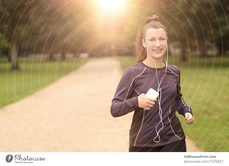 Hübsche Frau, die am Park mit Kopfhörern rüttelt Lifestyle Glück Sommer Musik Sport Joggen Erwachsene Landschaft Herbst Blatt Straße Bewegung Fitness hören