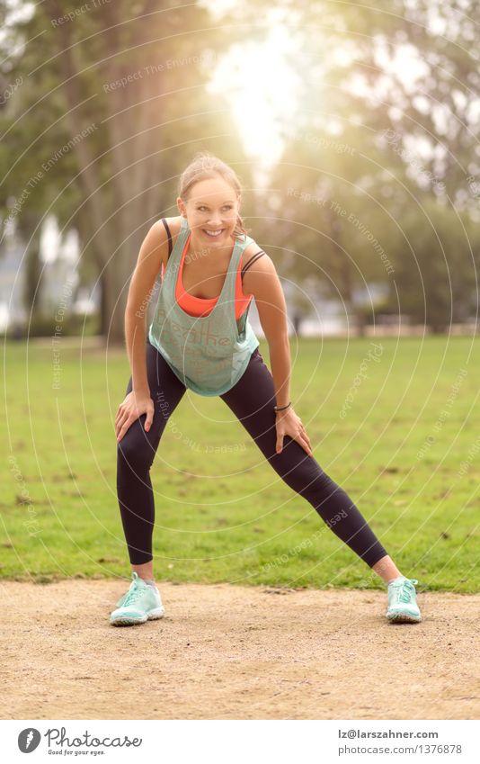 Athletische junge Frau, die Übungen ausdehnend tut Natur Sommer Erwachsene Glück Lifestyle Park Körper Fröhlichkeit Lächeln Fitness Wellness sportlich