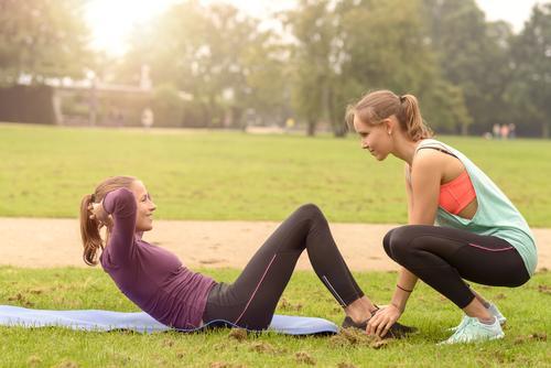 Die athletische Frau, die Locke tut, trainiert oben blau grün Erwachsene Gras Sport Glück Lifestyle Fuß Freundschaft Park Körper Aktion Arme Lächeln Fitness