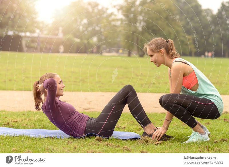 Die athletische Frau, die Locke tut, trainiert oben Lifestyle Glück Körper Sport Fitness Sport-Training Sportler Erwachsene Freundschaft Arme Fuß Gras Park