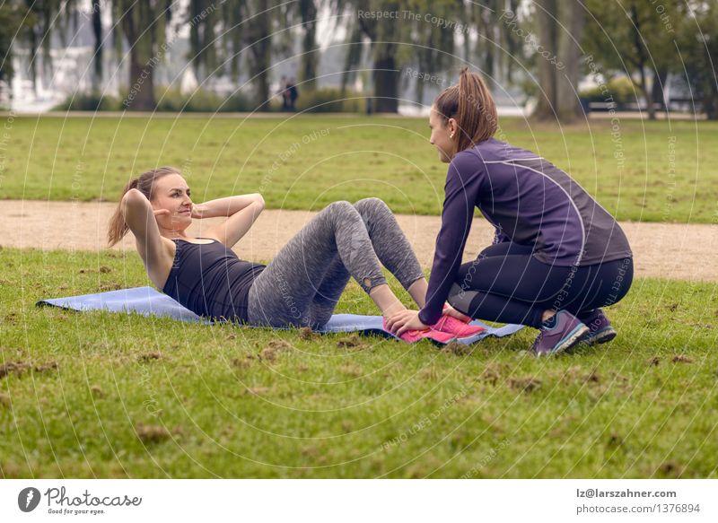 Das ernste athletische Frauenhandeln drückt Übungen hoch blau grün Erwachsene Gras Sport Glück Lifestyle Fuß Freundschaft Park Körper Aktion Arme Fitness