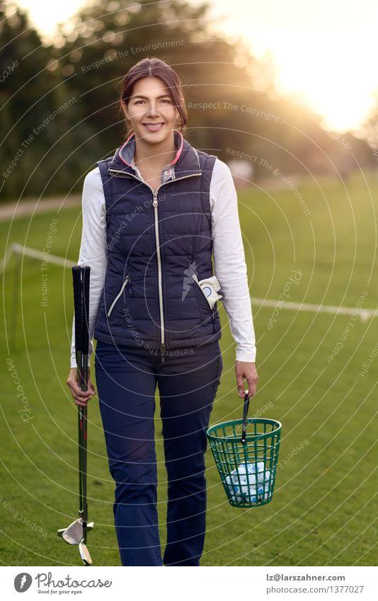 Tragende Bälle des Frauengolfspielers auf einer Driving Range Gesicht Freizeit & Hobby Spielen Golf Ball Erwachsene Herbst brünett Lächeln tragen dünn attraktiv