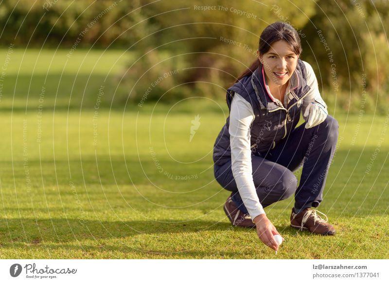 Lächelnder attraktiver junger weiblicher Golfspieler, der sich unten verbiegt Gesicht Erholung Freizeit & Hobby Spielen Sport Frau Erwachsene Natur brünett grün