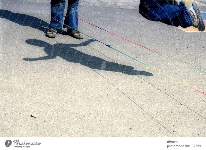 Gummitwist mit Schatten Freude Spielen Sportveranstaltung Kind Junge Arme Beine Jeanshose Schuhe springen dunkel hell hoch blau grau Körperbeherrschung hüpfen