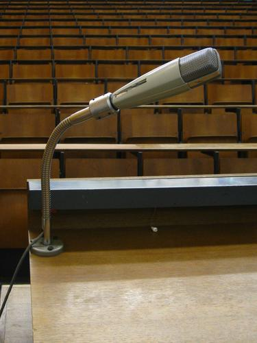 Ansprache Rede Hörsaal Audimax Studium Mikrofon grau braun Tisch Stuhl Sitzreihe Holzbank Raster Bestuhlung Steigung schwarz Erwartung leer Bildung Sitzung