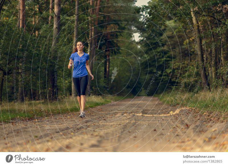 Athletische Frau, die heraus in einem Wald rüttelt Mensch Natur Jugendliche Einsamkeit Landschaft Mädchen Erwachsene Sport Lifestyle Sand Körper Aktion Musik